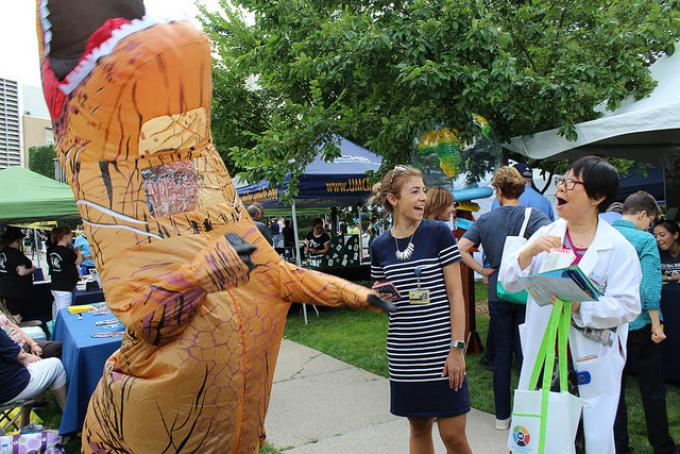 A person in a T-Rex costume laughs with two women at an outdoor event.