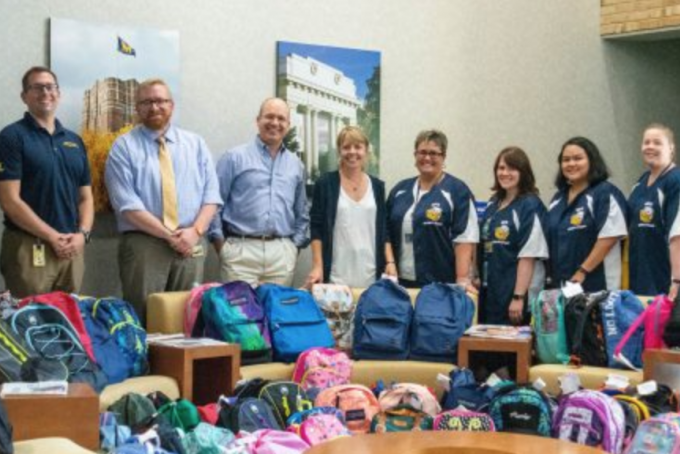 A group of people stands behind several backpacks that are full of school supplies.