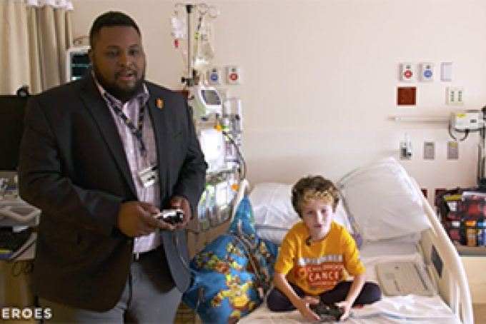 Ryan Henyard and a male pediatric patient play a video game.
