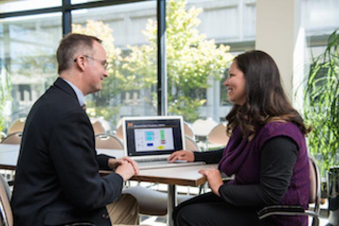 Two people talk next to a laptop.