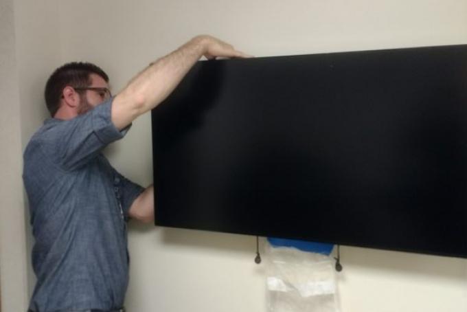 A HITS staffer installs a digital sign. (Photo by Rob Levitt)