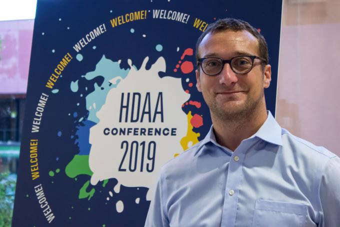 man standing in front of a HDAA poster