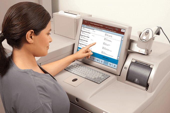 woman using automated medication dispensing system